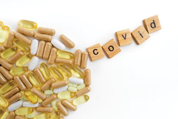 さまざまな錠剤の白い背景の上の木製の立方体の碑文covid