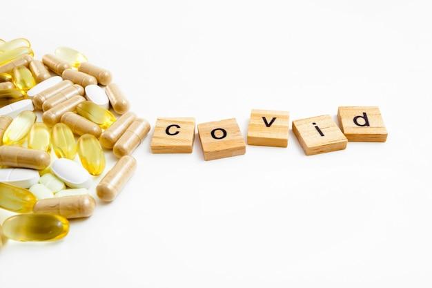 Надпись covid в деревянных кубиках на белом фоне различных таблеток