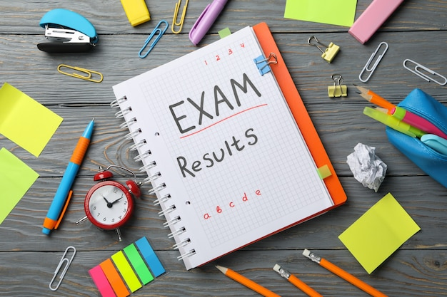 Inscription exam, results and stationary on wooden, top view