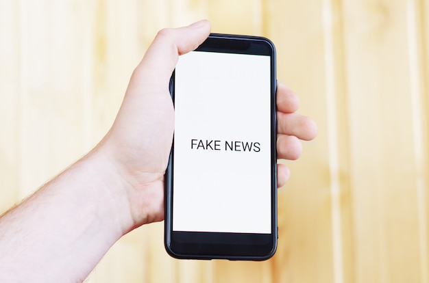The inscription fake news on a phone screen