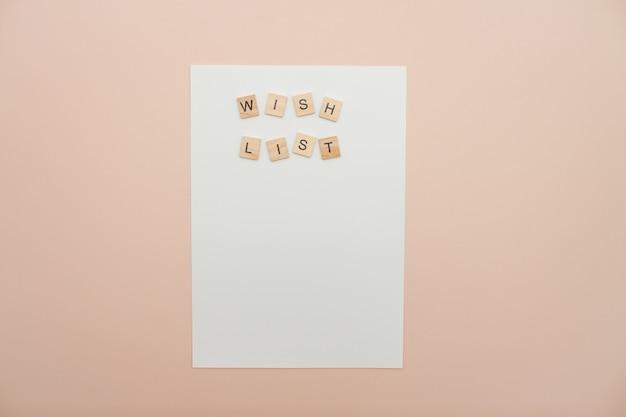 Надпись из списка желаний деревянных блоков на белом чистом листе бумаги. список желаний на новый год. письмо деду морозу