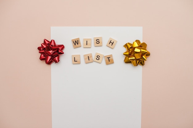 Inscription from wooden blocks wish list on a white blank sheet of paper. new year's wish list. letter to santa claus