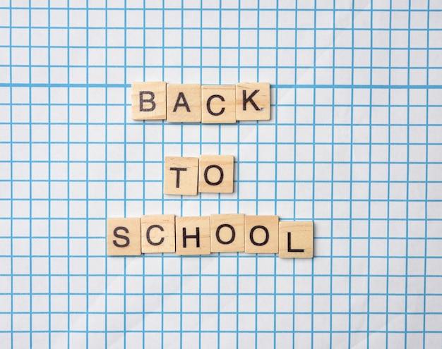 Надпись из деревянных букв обратно в школу на белом фоне листа в клетке, крупным планом