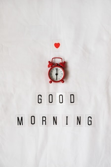 Inscription good morning, red analog clock, small heart on white rumpled sheets.