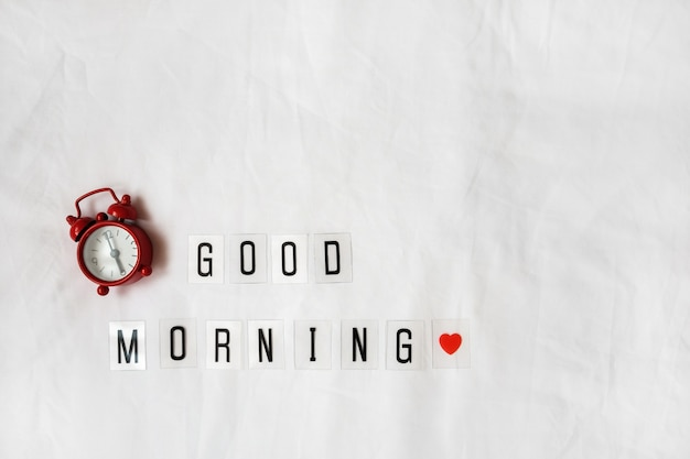 Inscription good morning, red analog clock on white rumpled sheets.