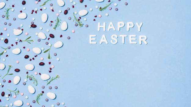 Надпись счастливой пасхи, украшенная драже и цветами