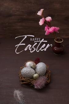Надпись счастливой пасхи с гнездом и яйцами на коричневом фоне с розовыми цветками и перьями. открытка на праздник пасхи