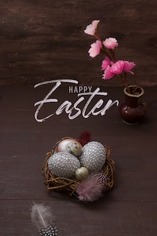 Inscription happy easter with nest and eggs on brown background with pink blossom flowers and feathers. greeting card for the easter holiday