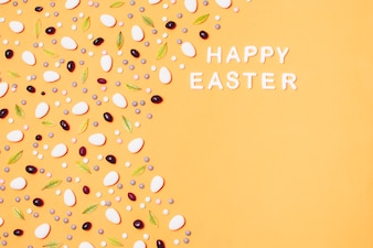 Надпись Счастливой Пасхи с посыпкой из драже и листьев
