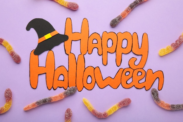 Inscription happy halloween with pumpkins on purple background. top view