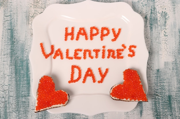 The inscription happy valentine's day from red caviar on a white plate with canapes, top view