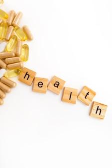 さまざまな錠剤の白い背景の上の木製の立方体の碑文の健康