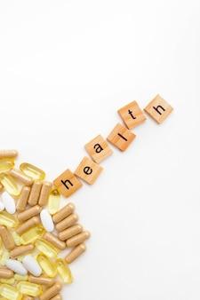 Надпись здоровье в деревянных кубиках на белом фоне различных таблеток