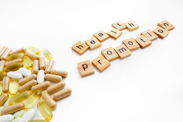 さまざまな錠剤の白い背景の上の木製の立方体の碑文の健康増進