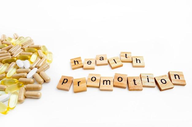 Надпись продвижение здоровья в деревянных кубиках на белом фоне различных таблеток