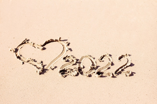The inscription  and the heart are drawn on the light sand new year symbol