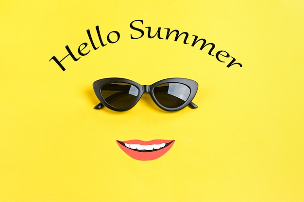 Inscription hello summer the sun with stylish black sunglasses, smiling mouth on yellow