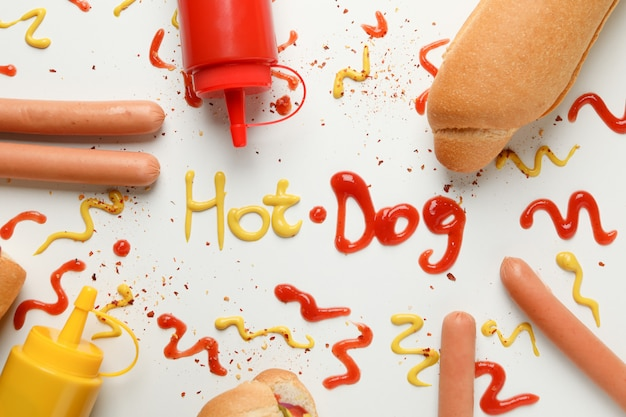 Inscription hot dog and ingredients for hot dog on white