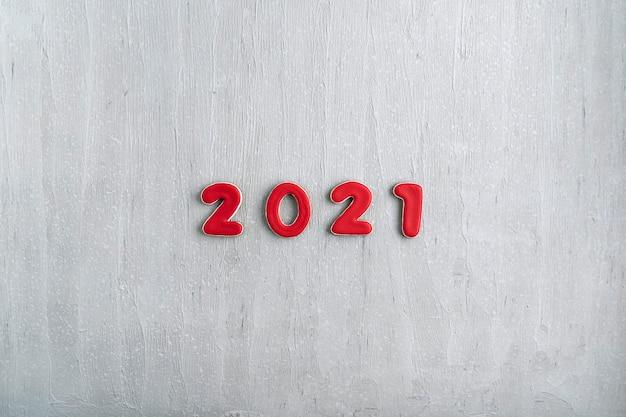 灰色の背景にジンジャーブレッドから赤い数字2021の碑文。 2021年の新年、コピースペース。