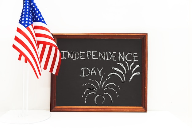 The inscription independence day in chalk on a slate board. american flags.  for independence day on july 4 (memorial day).