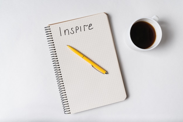 Inscription inspire in copybook. notepad, pen and coffee