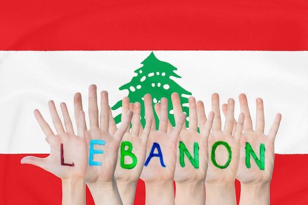 Inscription lebanon on the children's hands against the background of a waving flag of the lebanon