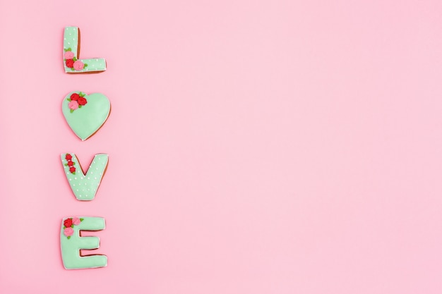 Inscription love by homemade cookies on pink background with copy space. holiday concept for wedding or valentines day.  minimal style composition.