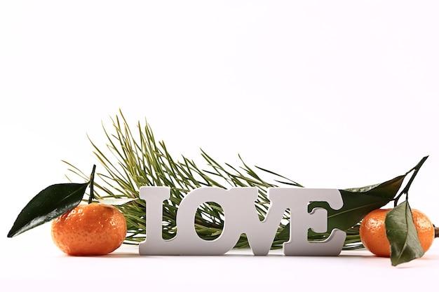 Надпись любовь мандарины еловые ветки на белом фоне