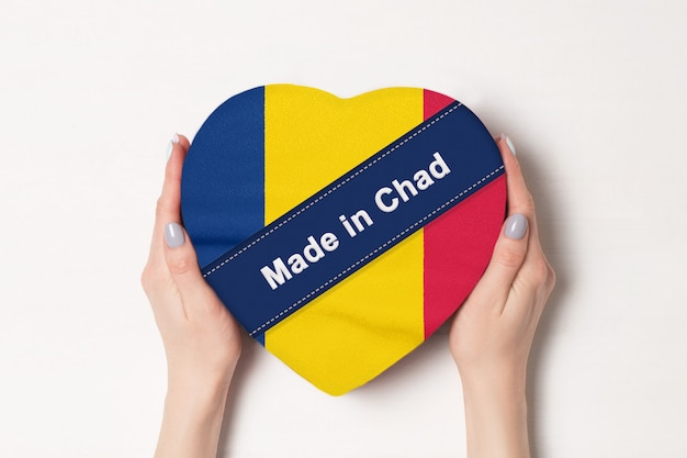 Inscription made in chad the flag of chad. female hands holding a heart shaped box.