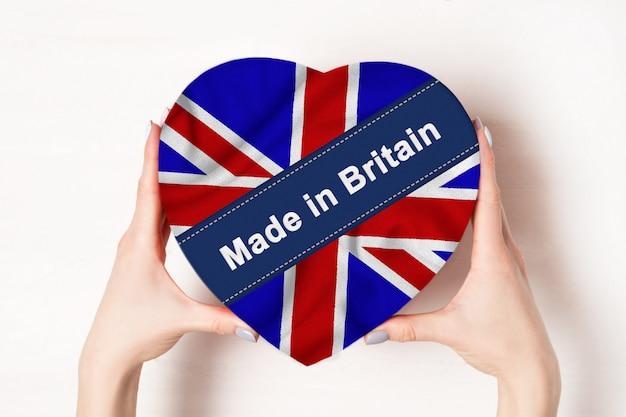 Надпись сделано в британии, флаг британии. женские руки, держа коробку в форме сердца. белый фон. место для текста