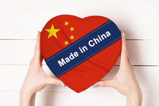 Надпись сделано в китае, флаг китая. женские руки, держа коробку в форме сердца. белый деревянный стол на стене. место для текста