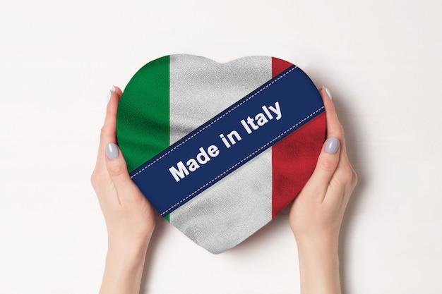 Надпись сделано в италии флаг италии. женские руки, держа коробку в форме сердца. белый фон.