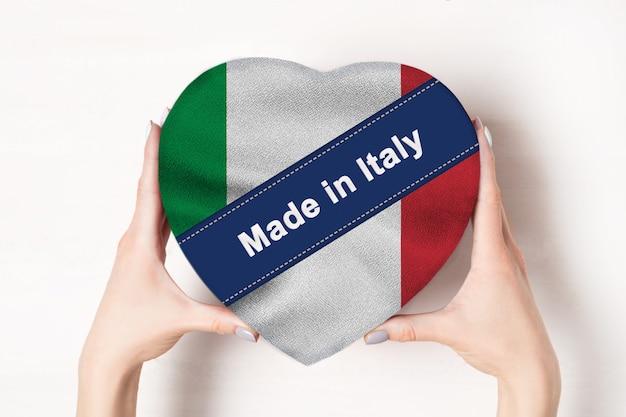 Надпись сделано в италии, флаг италии. женские руки, держа коробку в форме сердца. белая поверхность.