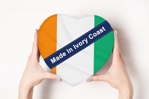 Inscription made in ivory coast, the flag of cote d'ivoire. female hands holding a heart shaped box. white .