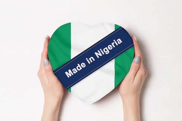 Inscription made in nigeria the flag of nigeria . female hands holding a heart shaped box. .