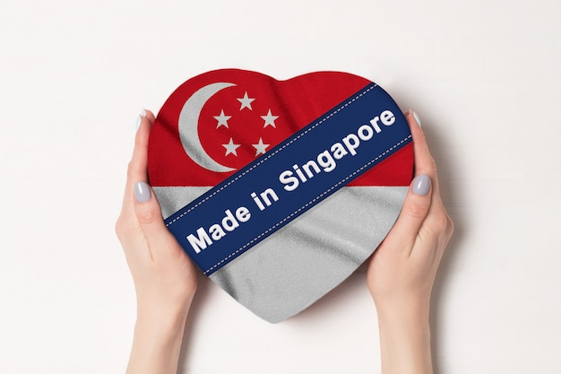 Inscription made in singapore the flag of singapore. female hands holding a heart shaped box.