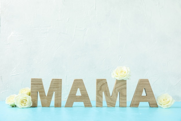 Inscription mama with white roses on blue table