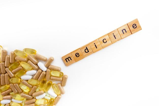 さまざまな錠剤の白い背景の上の木製の立方体の碑文の薬