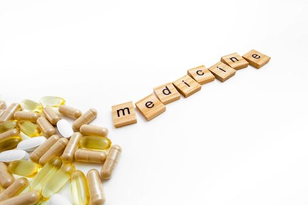 Надпись медицина в деревянных кубиках на белом фоне различных таблеток