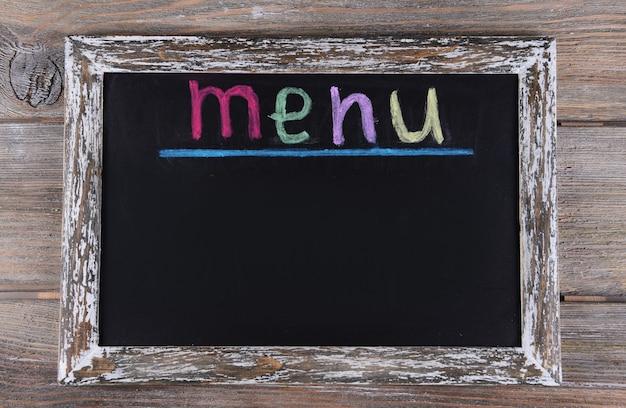 テーブルのクローズアップの黒板の碑文メニュー