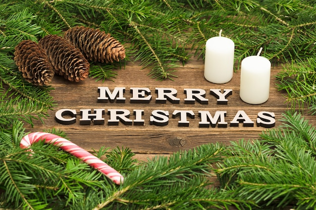 Inscription merry christmas on a wooden . frame of fir branches, cones and candles