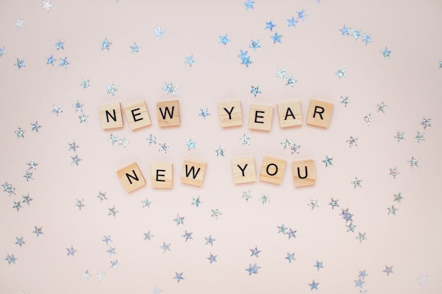 The inscription new year new you from wooden blocks with silver stars