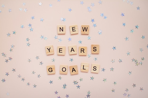 The inscription new years goals from wooden blocks with silver stars