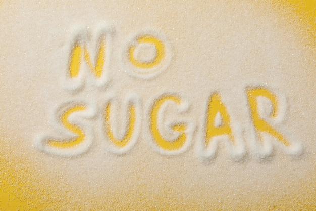 Надпись нет сахара из сахара на желтом фоне, вид сверху