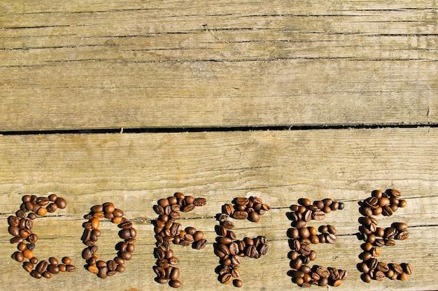 コピースペースと木の背景にコーヒー豆からコーヒーの碑文。上面図