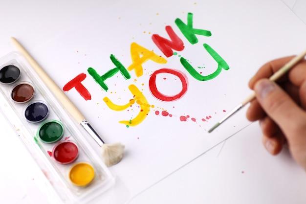 Надпись на белом листе бумаги акварелью «спасибо»