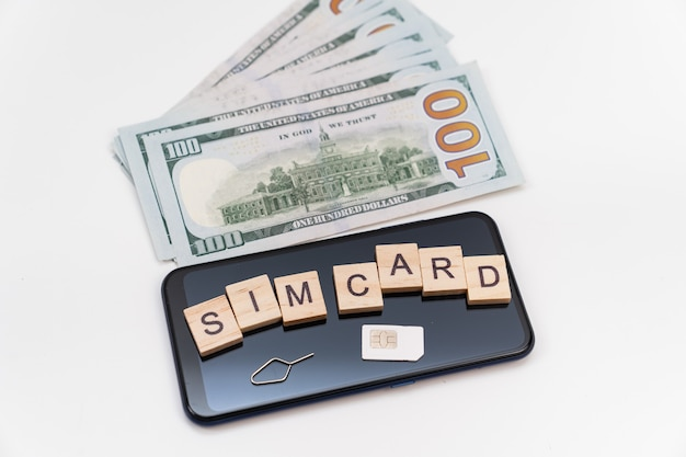 큐브, sim 카드, 스마트폰, 달러 지폐에 새겨진 비문. 모바일 및 인터넷에 대한 지불의 개념입니다. 일상 통신 비용