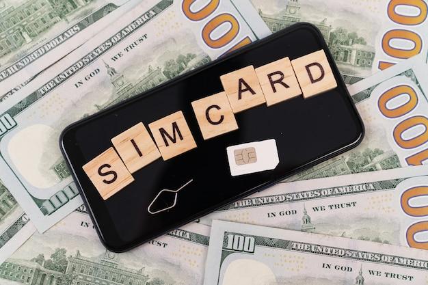 キューブやsimカード、スマートフォンの碑文、ドル紙幣。