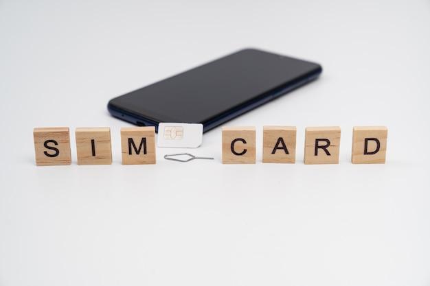 큐브, sim 카드, 키 클립 및 흰색 배경에 검은색 스마트폰에 비문