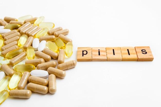 さまざまな錠剤の白い背景の上の木製の立方体の碑文の錠剤